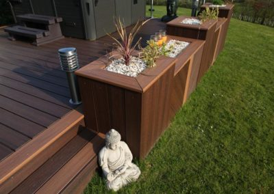 A Trex deck with steps leading to a lawn and several planters built into the face.