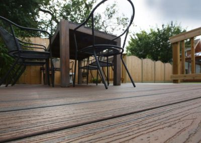 A Wide angled floor who of a dinning table positioned atop a Trex deck