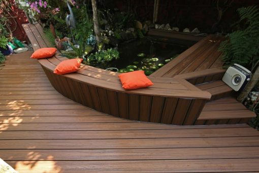 A Curved Bench surrounding a pond made from Trex Composite decking