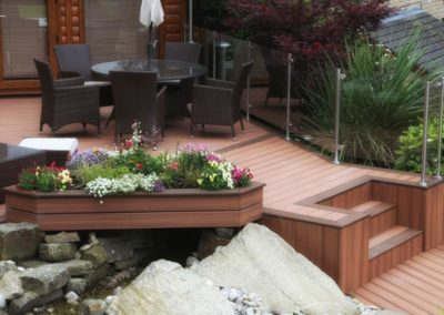 A Large triangle shaped planter containing flowers and made from Trex decking with a treat deck in the background